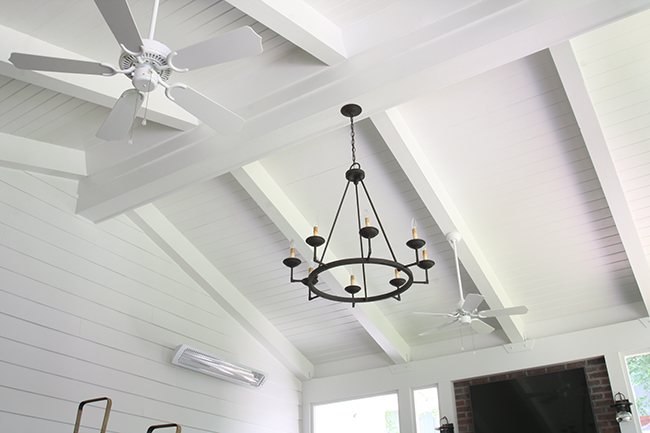 tongue and groove ceiling, shiplap walls and chandelier in the three season screened in porch