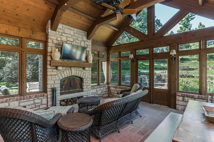 vaulted ceiling screened in porch with true stone fire place