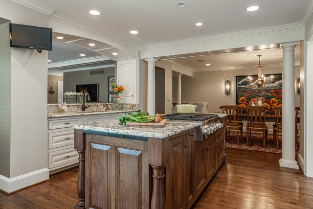 custom remodeled kitchen with granite island and opening to dining room