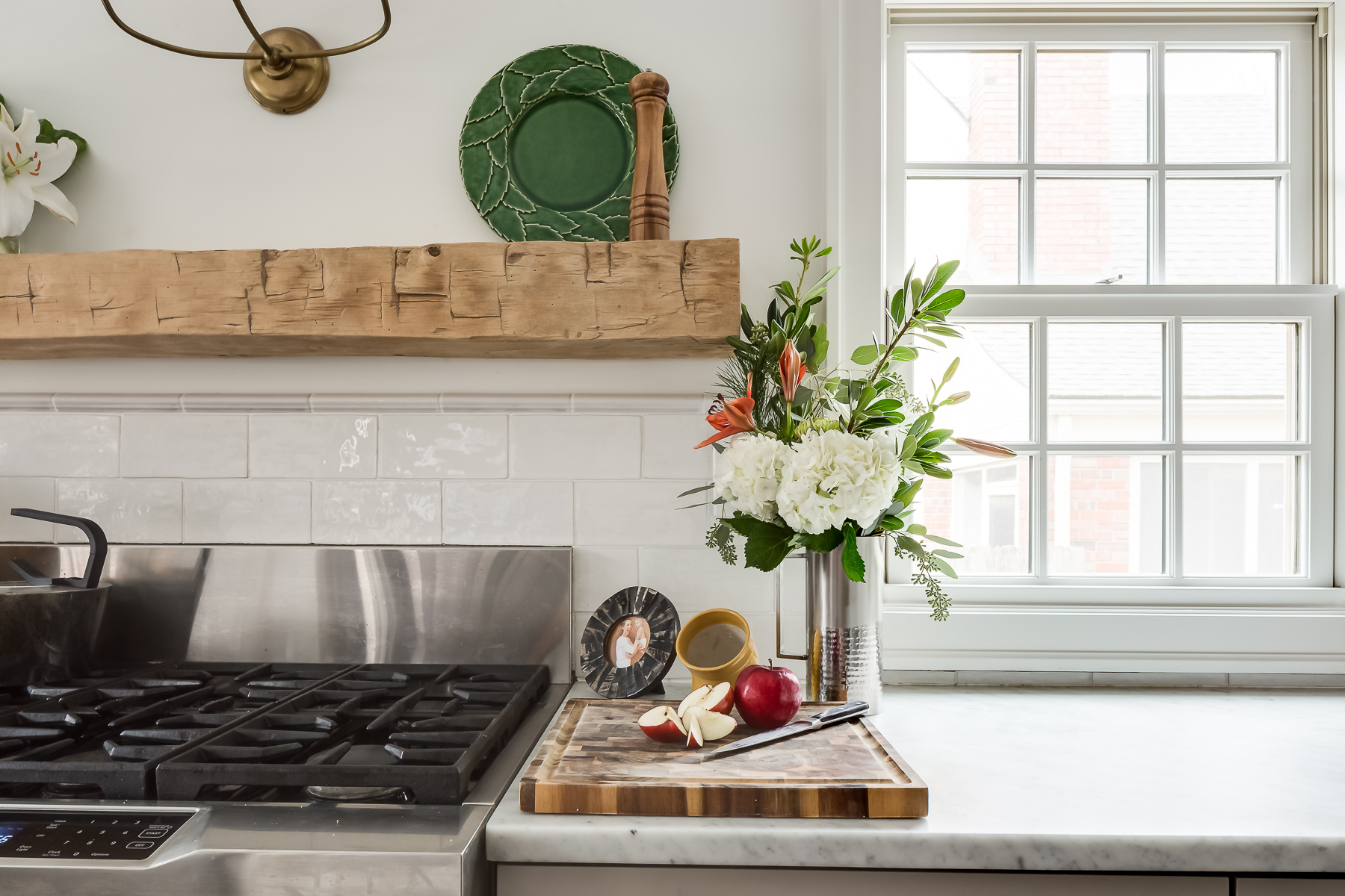 brass visual comfort wall sconce with reclaimed mantle and pro range stove in scovell wolfe kitchen