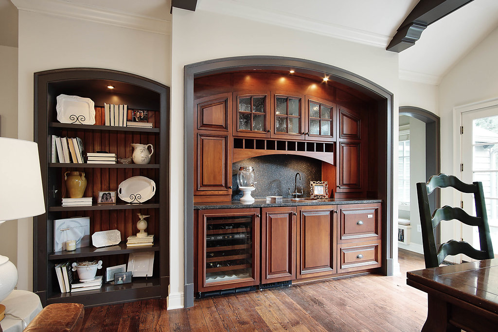 arch topped bookcases with stained wainscoting and wet bar