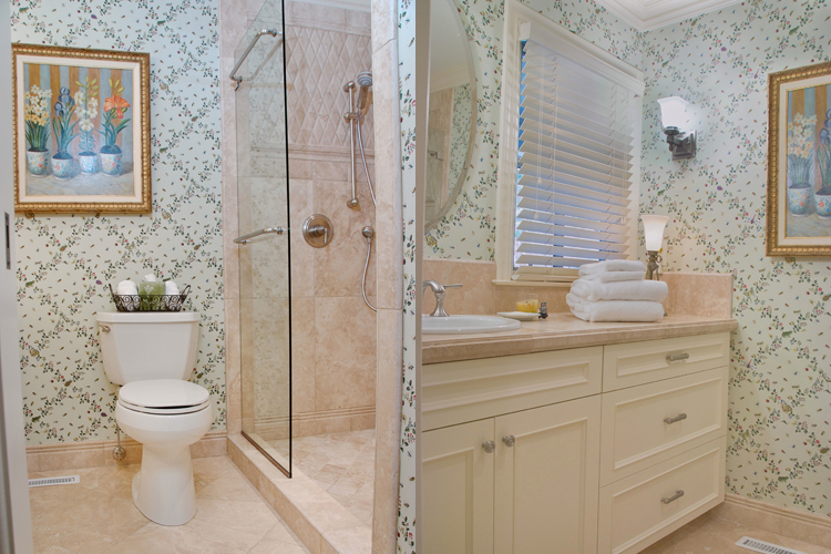 floral wallpaper in master bathroom with framless shower doors