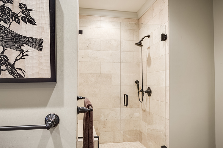 frameless shower door in master bathroom with custom shower pan and crown molding