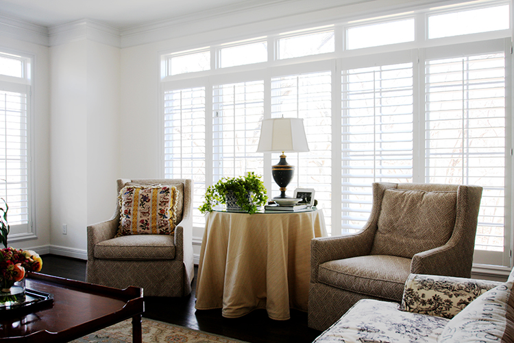 living room with plantation shutters and nell hills swivel chairs