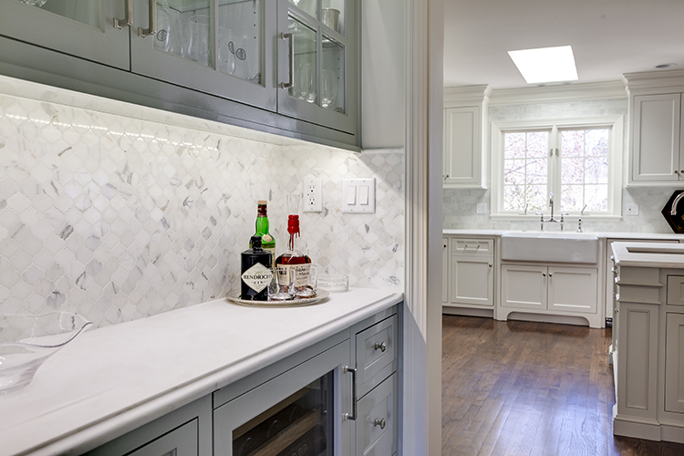 carrara marble penny tile backsplash with high gloss cabinets by scovell wolfe