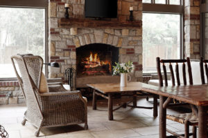 screened porch with stone and brick fireplace