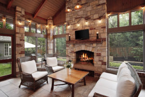stone and brick fireplace on screened porch by pool