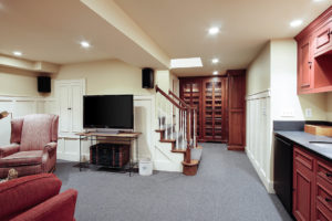 built in wine cabinets with wainscoting and exposed stair treads in the lower level