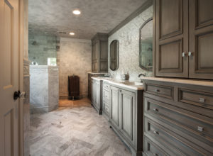 carrara marble mosaic master bathroom in sunset hills with herringbone floors