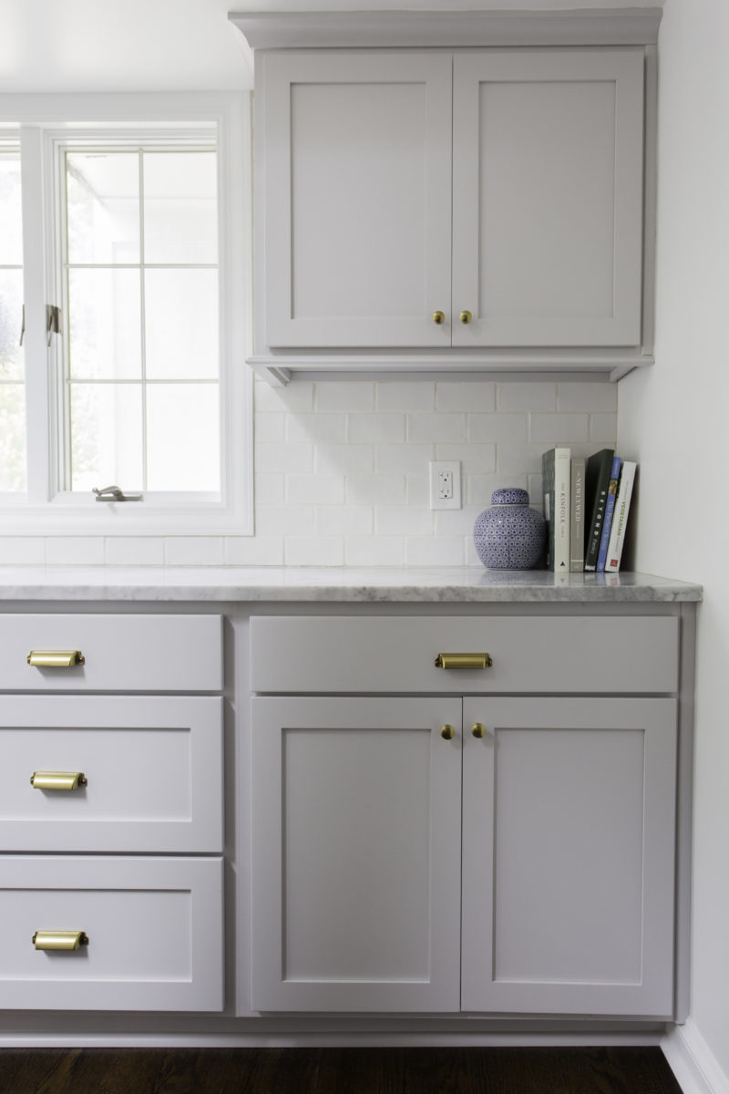 shaker style cabinets with brass pulls and glazed subway tile